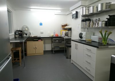 View of half of the Volunteer Friends kitchen. Includes ample workspace counter, shelving with various sized cooking pans etc, storage cupboards and microwave.