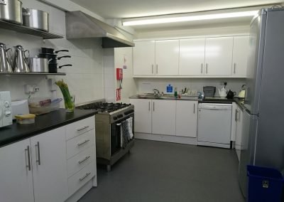 View of half of the Volunteer Friends kitchen. Includes large silver/grey fridge freezer, white dishwasher, dual sink bench. Also includes gas range and ample cupboard area.